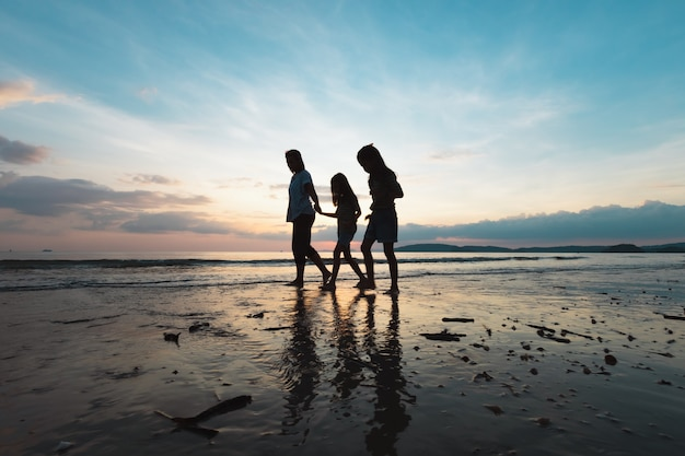Silhouette of asian mother and two daughters holding hand and walking on the beach together at the sunset time with beautiful sea and sky. family enjoy with nature concept.