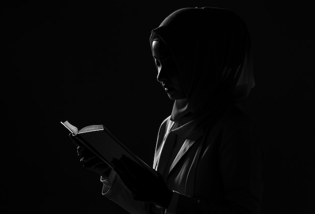 Силуэт азиатской мусульманской девушки в платье хиджаба молится с книгой на черном фоне