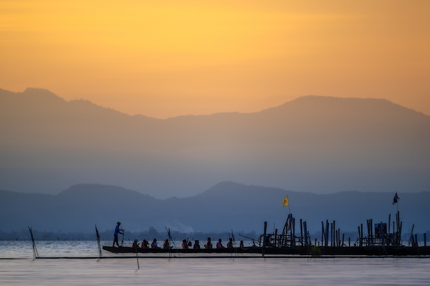 Silhouette of asian tourists relaxing on wooden boat.