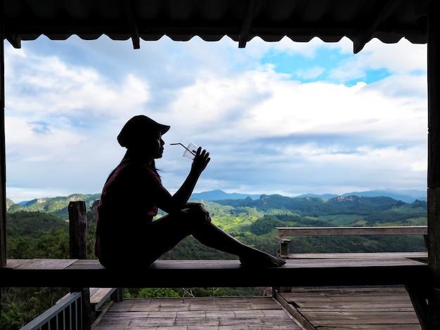 녹색 산과 푸른 하늘 배경 위에 아이스 커피를 마시는 실루엣 아시아 여자.