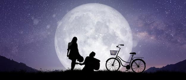 山で踊ったり歌ったりするカップルや恋人の夜の風景のシルエット