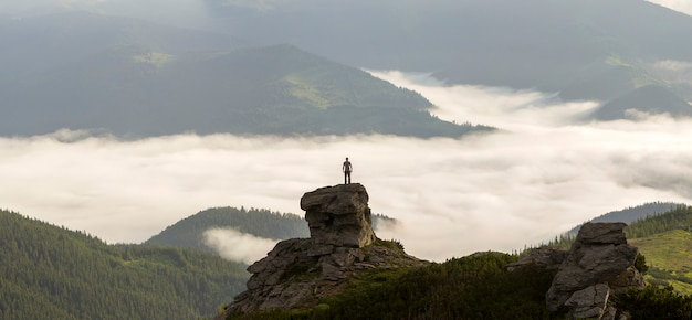 Silhouette of athletic climber tourist on high rocky formation on mountain valley filled with white puffy clouds and fog and covered with evergreen forest mountain slopes under clear sky background.