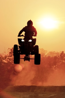 Silhouette atv jump on dirt tract