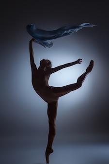 La silhouette della bella ballerina che balla con velo su sfondo blu scuro
