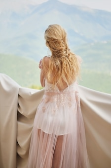 Silhouette of beautiful girl bride in a peignoir stands of the balcony overlooking the mountains