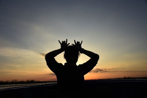 Silhouette of a beautiful girl standing on a background of gorgeous sunsets