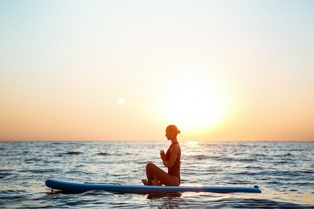 Siluetta di yoga di pratica della bella donna sulla tavola da surf ad alba.
