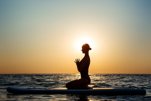 Silhouette of beautiful woman practicing yoga on surfboard at sunrise.