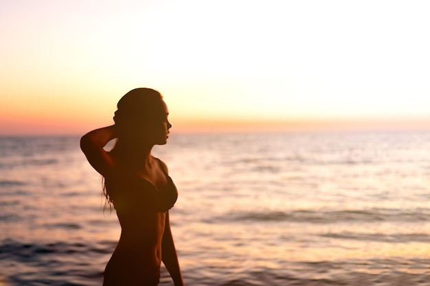 Silhouette of beautiful young gracile pensive woman with a freedom feeling at a beautiful sunset