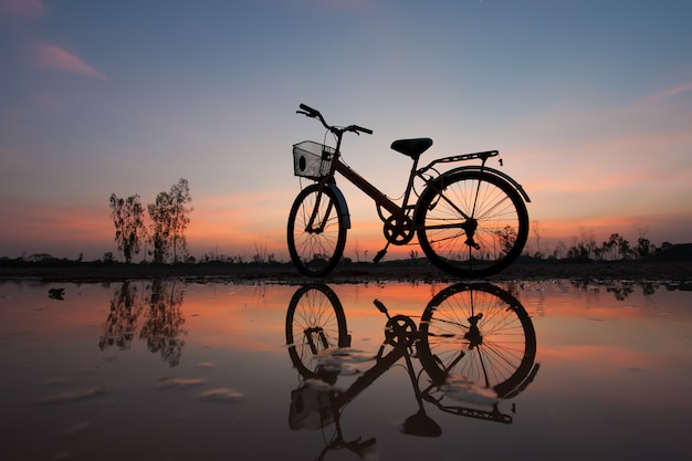 Silhouette bicycle at sunset and reflection