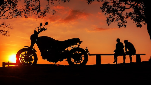 Silhouette big bike motorcycle with couple sitting together on mountain peak at sunset