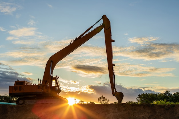 Silhouette of big excavator digging the soil on site