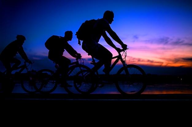 Silhouette of a bike cyclists on sky on sunset