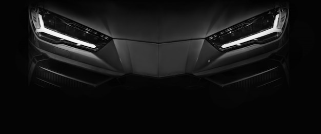 Silhouette of black sports car with led headlights on black