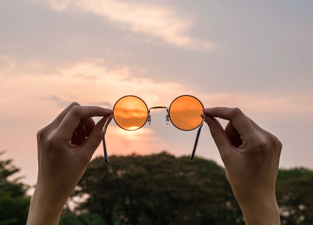 Silhouette,blurry,art tone of orange sunglasses with evening sky background