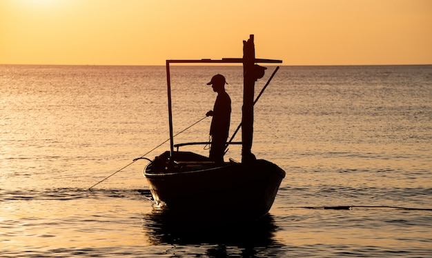 Silhouette of boat and fisherman sunset time.