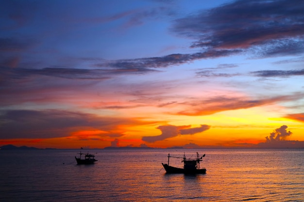Silhouette boat on the sea and colorful sunset