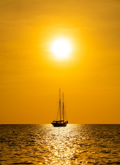 Silhouette boat in sea and ocean with beautiful sunset sky
