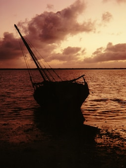 Silhouette of a boat on a shore near the water under a pink sky at lamu, kenya