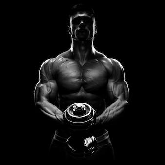 Silhouette of a bodybuilder pumping up muscles with dumbbell
