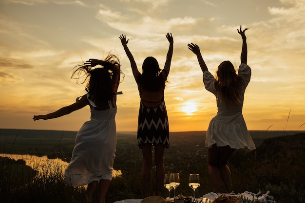 Silhouette of bouncing happy girls with curly hair in summer dress with perfect sunset.