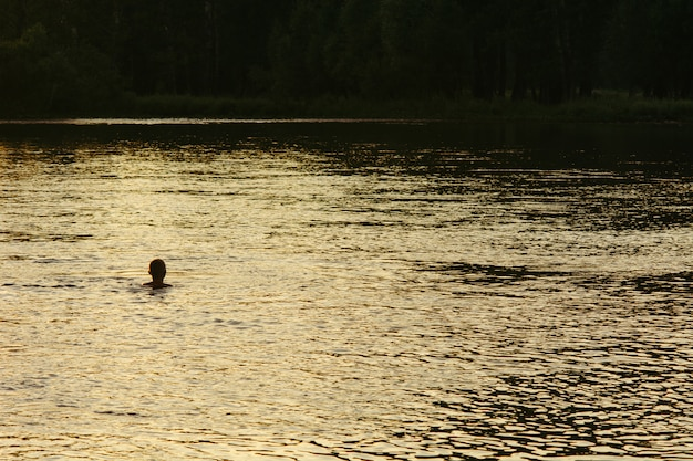 Silhouette of a boy bathed in a mountain river. evening.