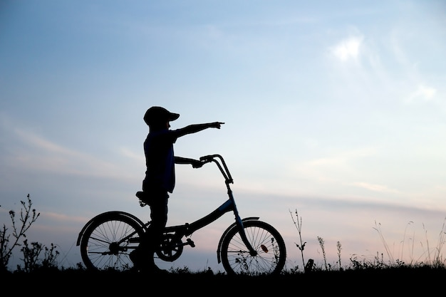 A silhouette of a boy on a bicycle in nature
