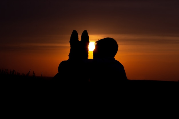 Silhouette of boy and dog hugging at sunset