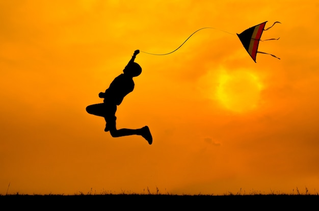 Silhouette of a boy jumping with kite to fly