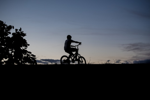 Silhouette of a boy riding a bicycle