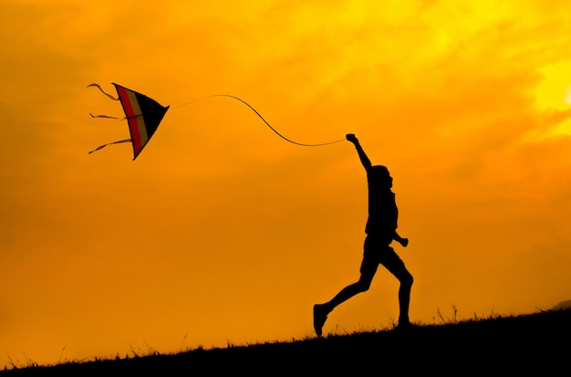 Silhouette of a boy running with kite to fly. sunset.