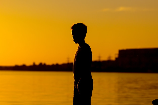 Silhouette of a boy standing near the river at sunset.