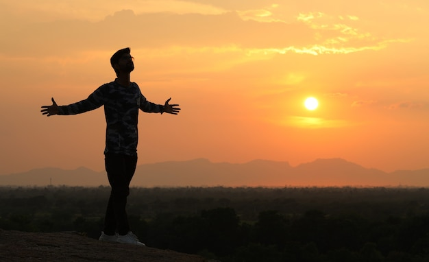 夕日の背景に一人で歩くシルエットの少年