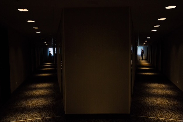Silhouette of bride and bridegroom in dark corridor