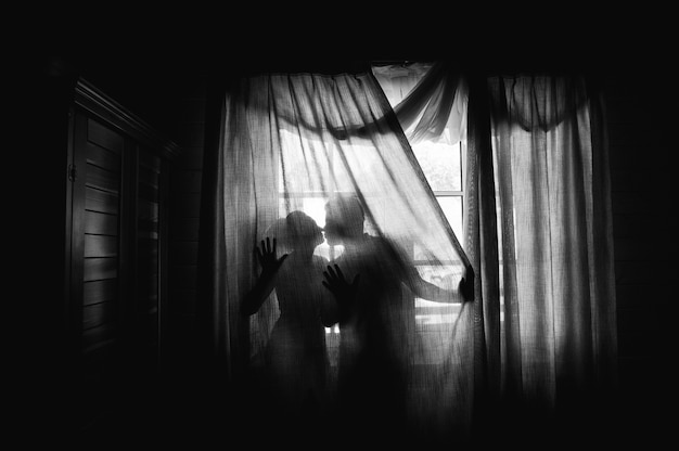 Silhouette of a bride and groom on the background of a window with curtains.