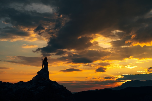 Silhouette of the bride standing on the rocks in the mountains at sunset