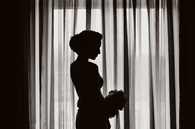 Silhouette of a bride with wedding bouquet at the window