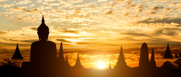 Silhouette of buddha on golden temple sunset background
