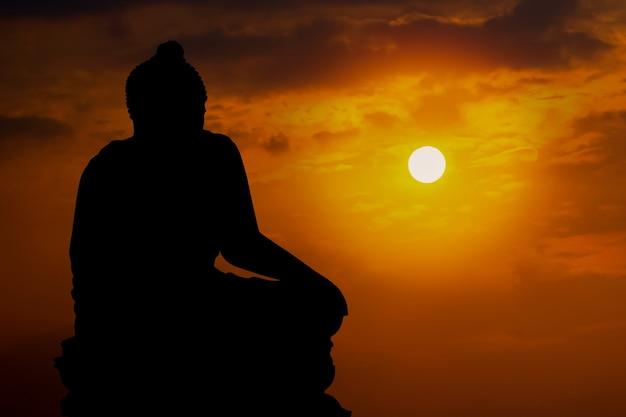 불교의 일몰 배경 믿음에 실루엣 부처님 동상