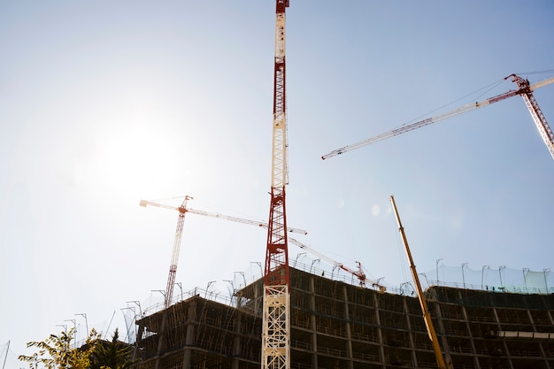 Silhouette of buildings under construction against blue sky in sunlight