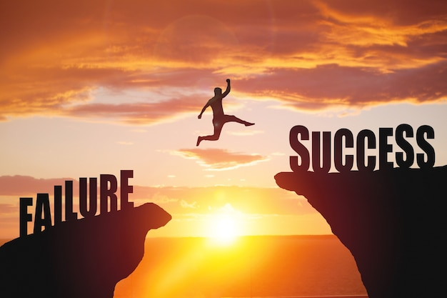 Silhouette of business man jump to success text over a beautiful high view mountain surface