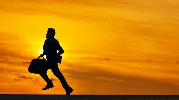 Silhouette business man run with laptop briefcase at pedestrian with sunrise sky
