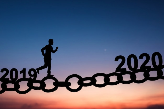 Silhouette of business man walking and running on chain bridge from 2019 to 2020