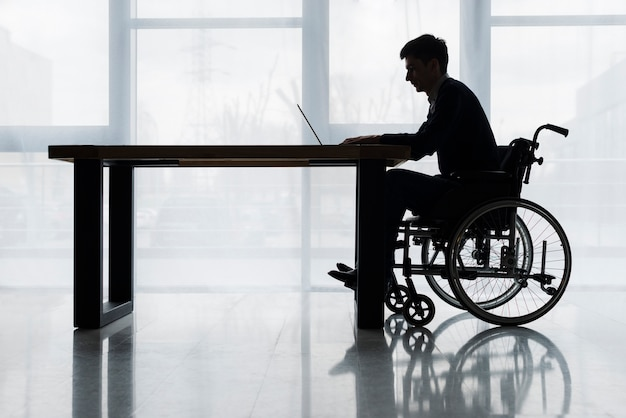 Silhouette of a businessman sitting on wheelchair using laptop on table in front of window