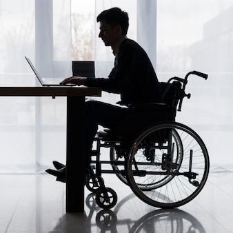 Silhouette of a businessman sitting on wheelchair using laptop on table