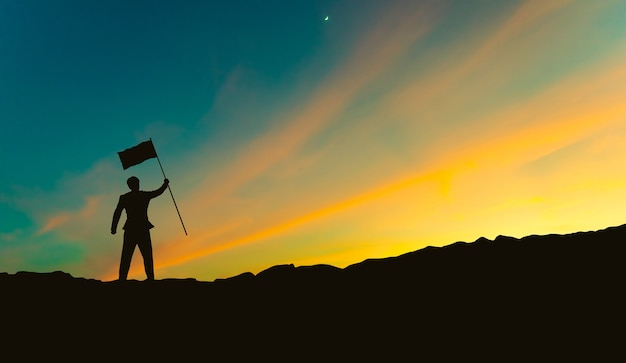 Silhouette of businessman with flag on mountain top over sunset sky