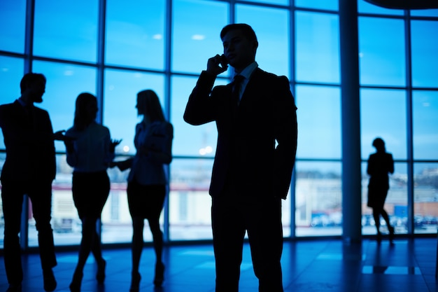 Silhouette of busy man with co-workers background