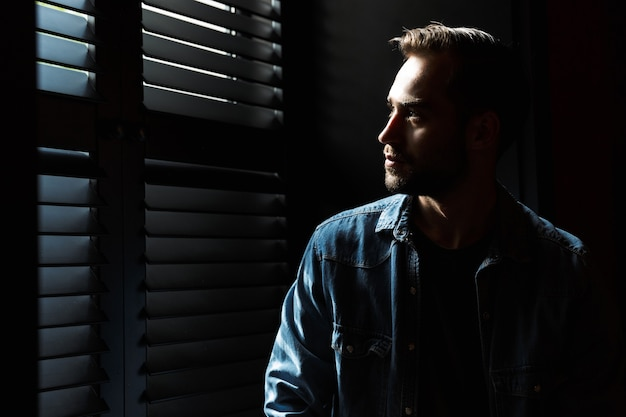 Silhouette of caucasian thoughtful man standing in dark room against the sunlight from window at shadow blinds
