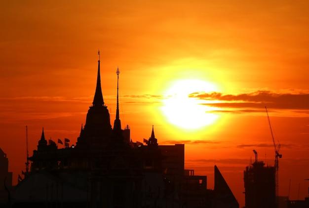 Silhouette of the chedi phu khao thong golden mount of wat saket temple at dawn, the iconic landmark of bangkok, thailand