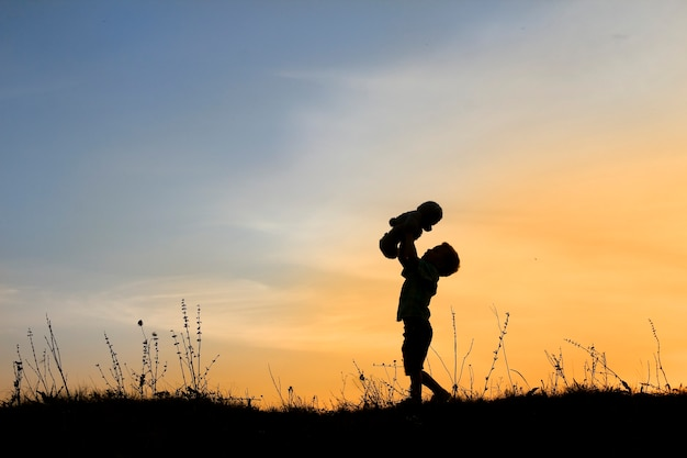 Silhouette of child boy with bear on sunset